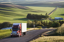 Commercial Truck Driving On Road Passing Through Field
