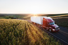 Commercial Truck Driving On Road Passing Through Wheat Fields