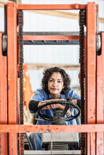 Portrait Of Woman Sitting In Forklift Truck