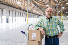 Portrait Of Senior Man Standing With Hand Truck In Warehouse