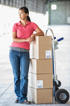 Woman Standing With Hand Truck...