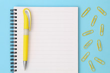 Back To School Creative Concept. Notepad With Yellow Pen And Clips On A Blue Background. Top View Of A Flat Lay.