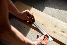 Carpenter Measuring Plank Of Wood With Metal Ruler