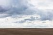 Storm clouds over barren farmland