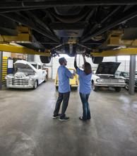 Mechanics Examining Car In Automobile Repair Shop