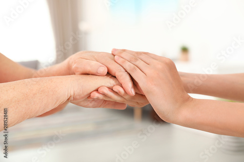 Poster Yoga school People holding hands together on blurred background, closeup. Help and elderly care concept