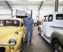 Portrait Of Mechanic Standing Near Car In Automobile Repair Shop