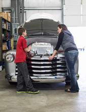 Woman Talking With Her Son About Car Engine In Automobile Repair Shop