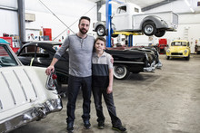 Portrait Of Man With His Son Standing In Automobile Repair Shop
