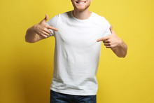 Young Man Wearing Blank T-shirt On Yellow Background, Closeup. Mockup For Design