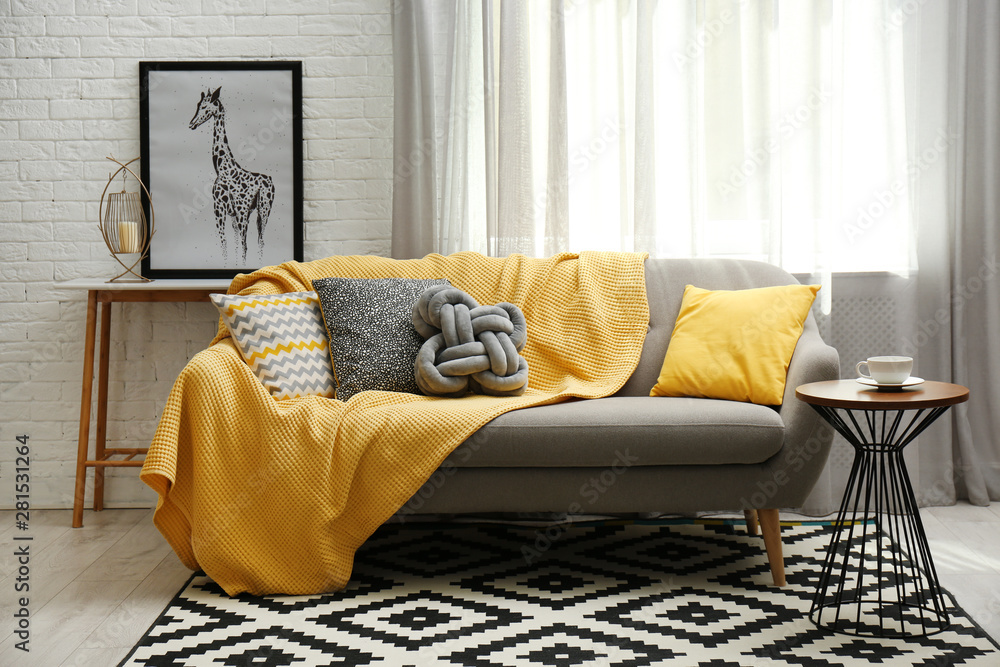 Fototapeta Stylish living room interior with soft pillows and yellow plaid on sofa