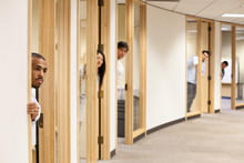 Business People Peeping Through Doorway In Office Corridor