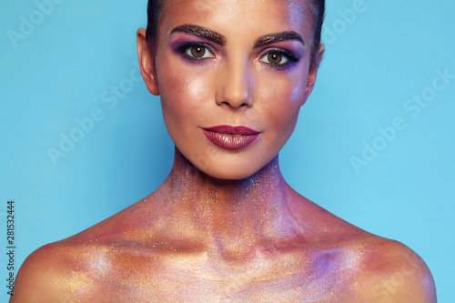 Fotografía  Sexy young woman with glitter makeup on blue background