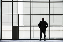 Rear View Of Businessman Looking Through Window In Convention Center