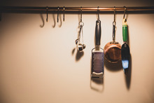 Close Up Of Kitchen Utensils Hanging On Copper Pipe