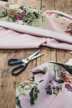 Close Up Of Scissor And Pink Floral Fabric On Wooden Table