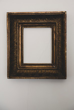 Close Up Of Empty Gilded Antique Picture Frame On White Wall