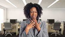 Black African American Businesswoman In An Office Looking Sick With Sore Throat.  She Is An Owner Or An Executive Of The Workplace.  Depicts Careers And Startup Business.