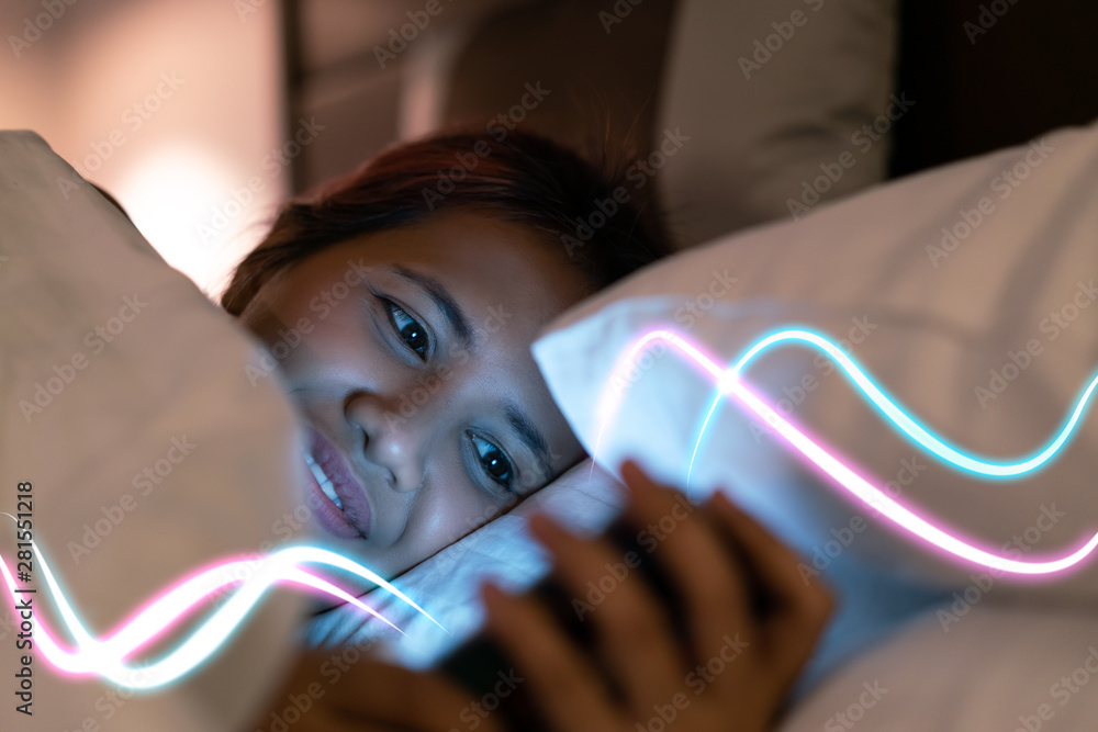 Fototapeta Asian social media lifestyle woman using smartphone in bed with glowing light streaks - Millennial girl online at night with latest generation internet download speed - Web and technology concept