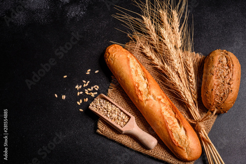 Fototapeta Fresh fragrant bread with grains and cones of wheat against a dark background. Assortment of baked bread on wooden table background obraz