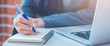Woman hand is writing on a notepad with a pen and have a laptop computer on the desk in the office.Web banner.