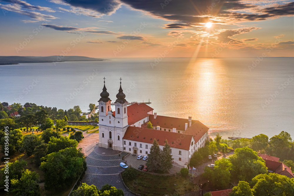 Fototapeta Tihany, Hungary - Aerial skyline view of the famous Benedictine Monastery of Tihany (Tihany Abbey) with beautiful colourful sky and clouds at sunrise over Lake Balaton