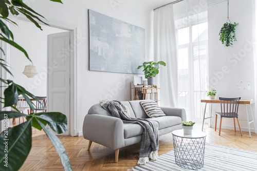 Fotografía  Stylish scandinavian living room with design furniture, plants, bamboo bookstand and wooden desk