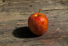 Red  Withered Apple On A Wooden Table.