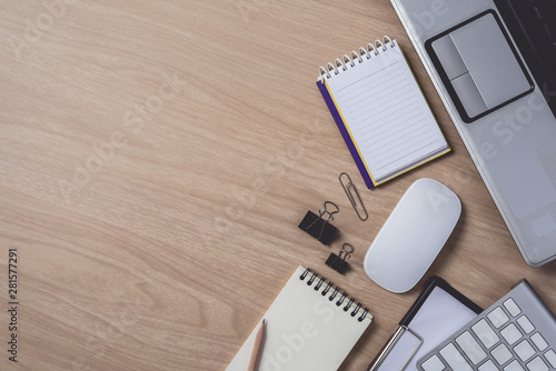 Workspace with diary or notebook and clipboard, laptop, mouse computer, keyboard, smart phone, pencil, pen on wooden background