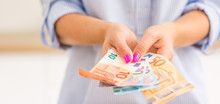 Hands Of Young Woman Holding Euro Banknotes