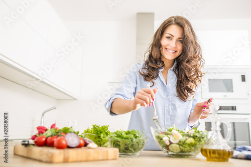 Papel de parede Young woman preparing vegetable salad in her kitchen