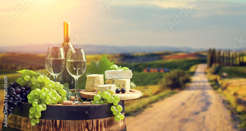 Spoed Foto op Canvas Wijn wine bottle and wine glass on wodden barrel. Beautiful Tuscany background