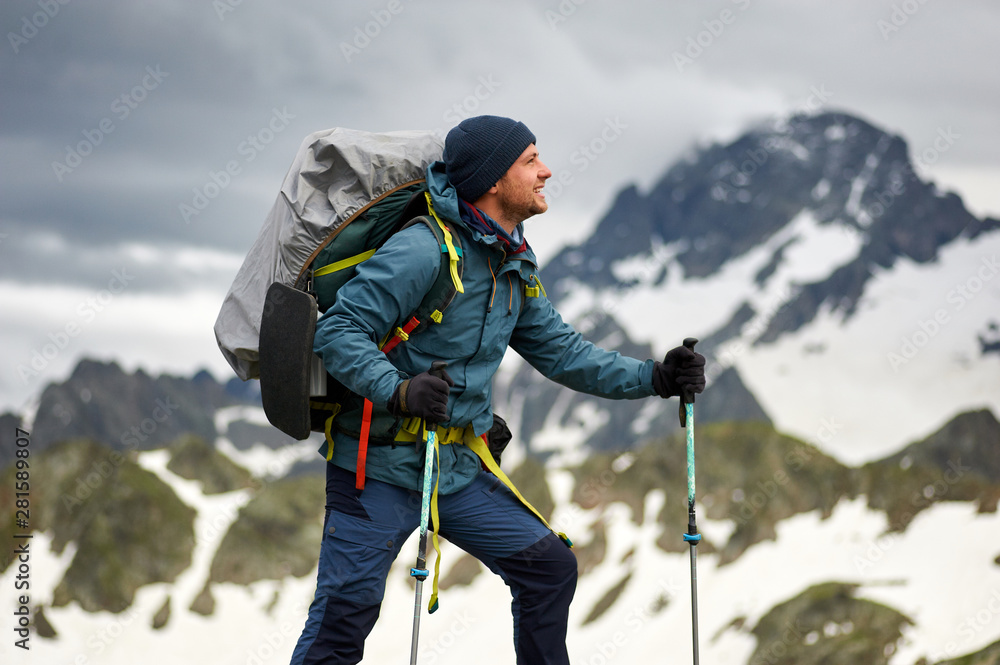 Fototapety, obrazy: Hiker man stands on the cliff against the top of a mountain. Man has a backpack and trekking poles. Mountain trekking. Copy space