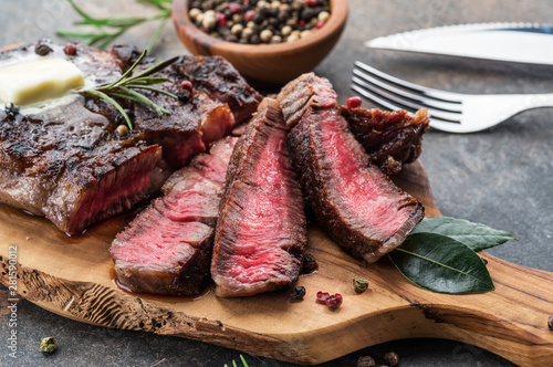 Photo sur Aluminium Pays d Europe Medium rare Ribeye steak with herbs and a piece of butter on the wooden tray.