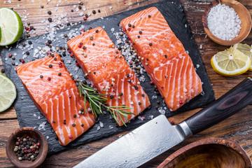 Fresh salmon fillets on bla...