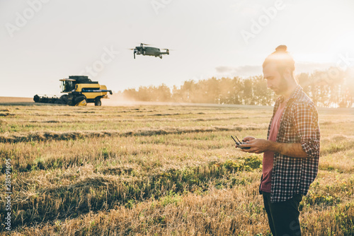 Farmer navigating drone above farmland with combine at the background Fototapet