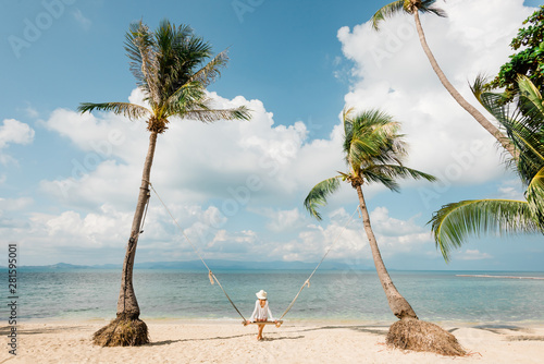 A girl in a white hat sits on a swing among the palm trees on Leela Beach on Koh Wallpaper Mural