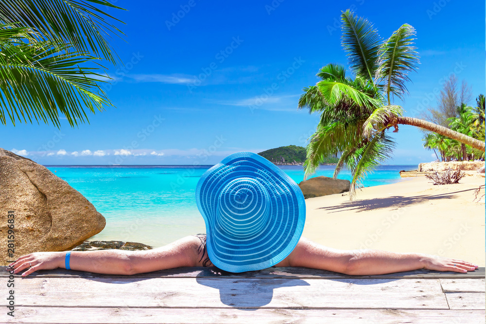 Fototapeta Woman in hat on tropical holidays at the beach