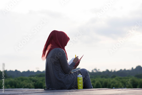portrait of hijab  woman was sitting on the board in the sun in a beautiful mang Canvas Print