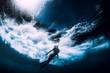 Woman dive underwater with big ocean wave.