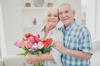 Photo of two adorable aged people hugging pair anniversary holiday surprise big red tulips bunch flat indoors