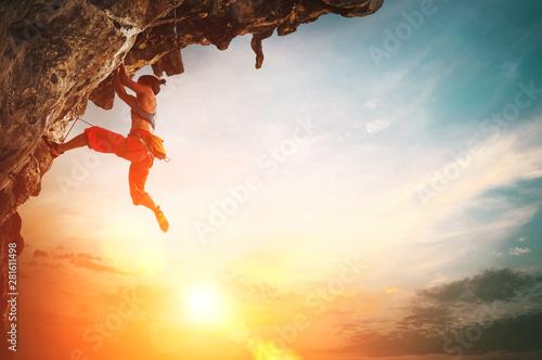 Obraz na plátně  Athletic Woman climbing on overhanging cliff rock with sunset sky background