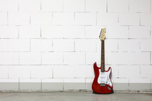 Red Electric Guitar Stands To The Right Against White Brick Wall