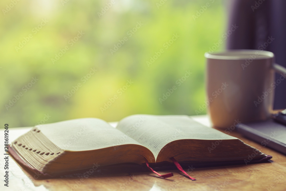 Fototapety, obrazy:  Open bible with a cup of coffee for morning devotion on wooden table with window light