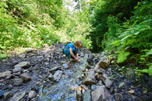Boy Playing Into Te Forest Stream At Summer Day