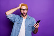 Leinwanddruck Bild Photo of cool guy holding telephone reading bad news wearing specs casual denim outfit isolated violet background