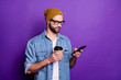 Leinwanddruck Bild Cool handsome guy holding telephone drinking coffee casual outfit isolated violet background