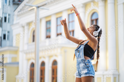 Beautiful mixed race girl listening to music in headphones and dancing. her arms are raised up - 281626250