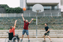 Man In Wheelchair Doing Sport With Friends