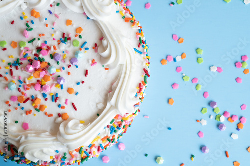 Photo  Top View of a cake with white icing and colorful sprinkles on a light blue backg